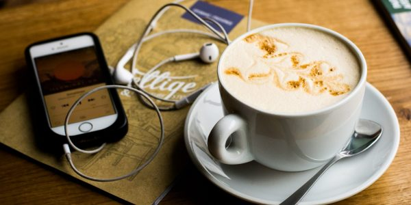 cup of cappuccino with headphones and iPhone on wooden table